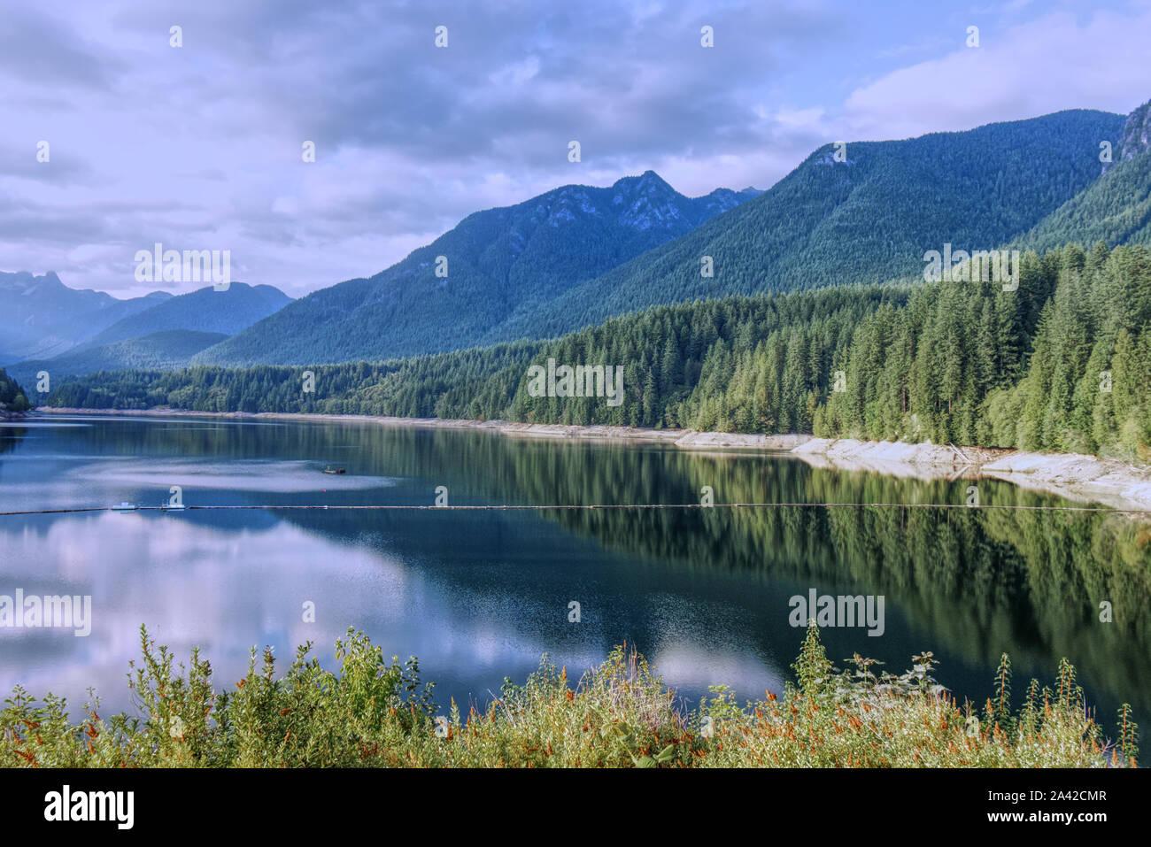 Una vista escénica de Cleveland embalse rodeado de montañas al atardecer, North Vancouver, Canadá Foto de stock