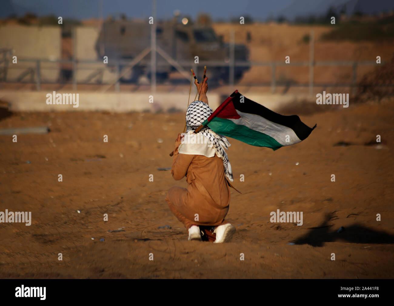 Un manifestante palestino utiliza un tirachinas a arrojar piedras durante una manifestación anti-Israel para poner fin a los años de asedio en la frontera Israel-Gaza en el sur de Gaza. Foto de stock