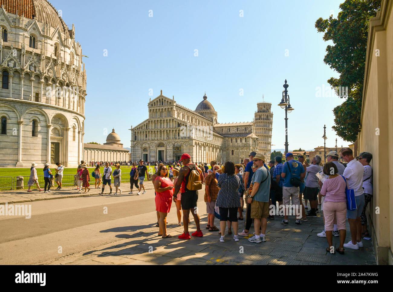 Un grupo de turistas descansando en la sombra de un muro en la famosa Piazza dei Miracoli con la torre inclinada en un caluroso día de agosto, Pisa, Toscana, Italia Foto de stock