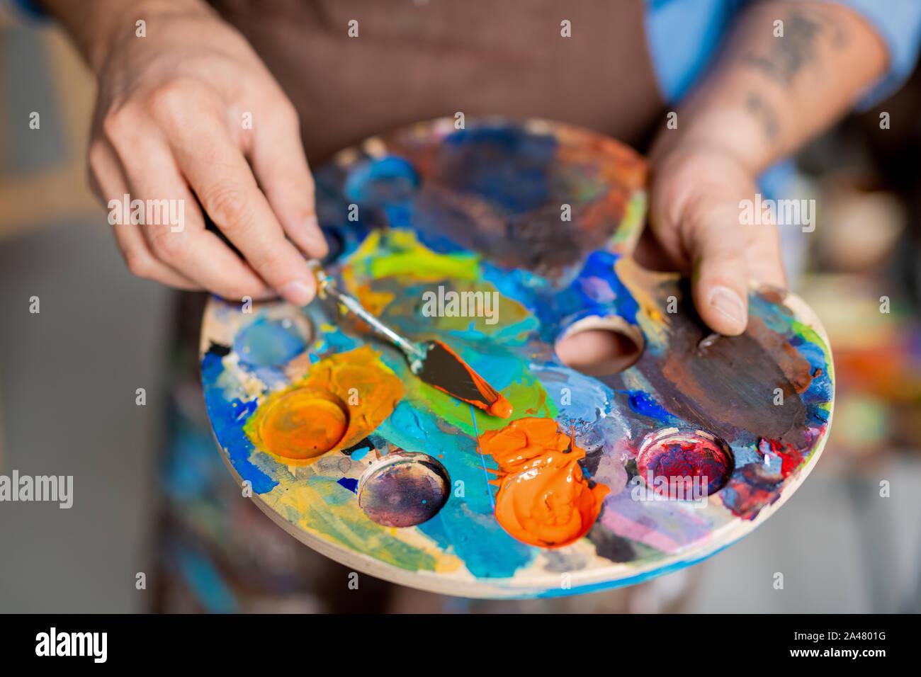 Mano de mezclado de pinturas en la paleta de pintor con pequeño instrumento antes de pintar Foto de stock