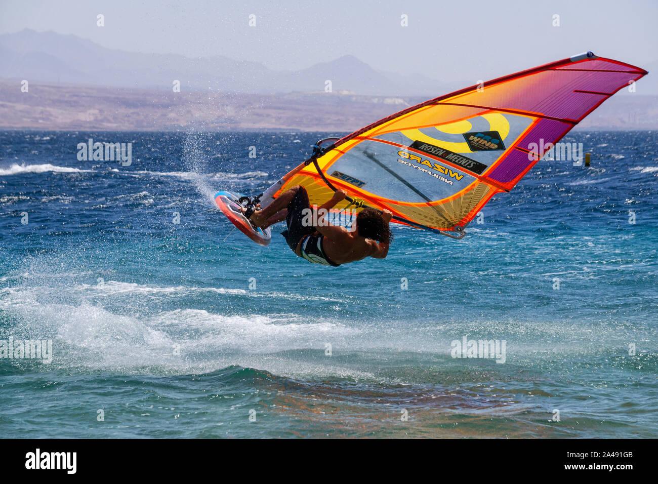Eilat, Israel - 12 de abril de 2019: el hombre es aventurero disfrutar de deportes acuáticos, windsurf, en el Mar Rojo durante un día soleado. Foto de stock