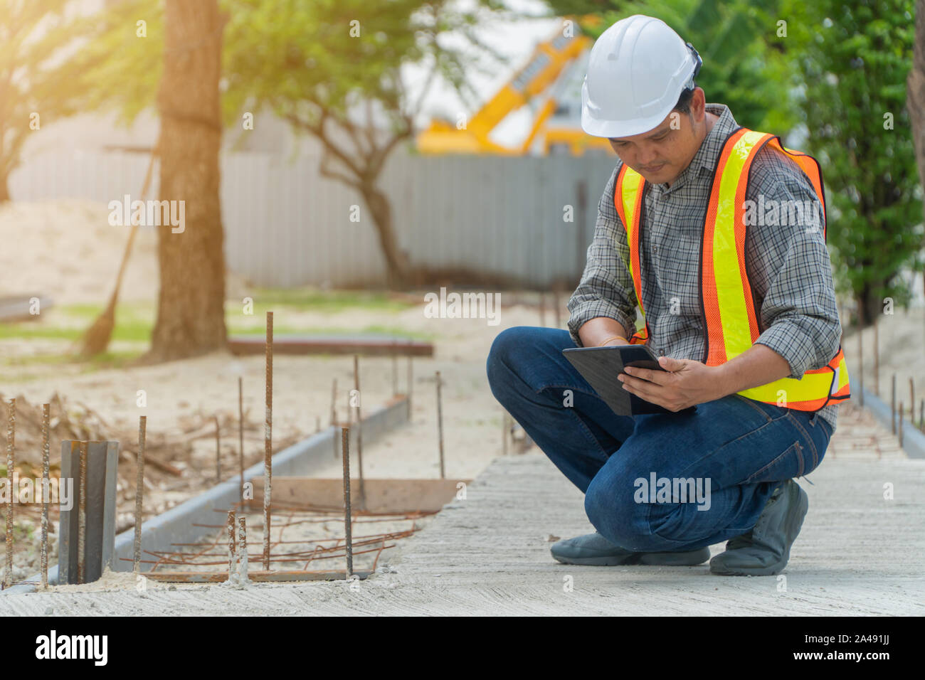 Ingeniería, usar un casco y sosteniendo las tabletas, sentarse a revisar la estructura del corredor en el parque Foto de stock