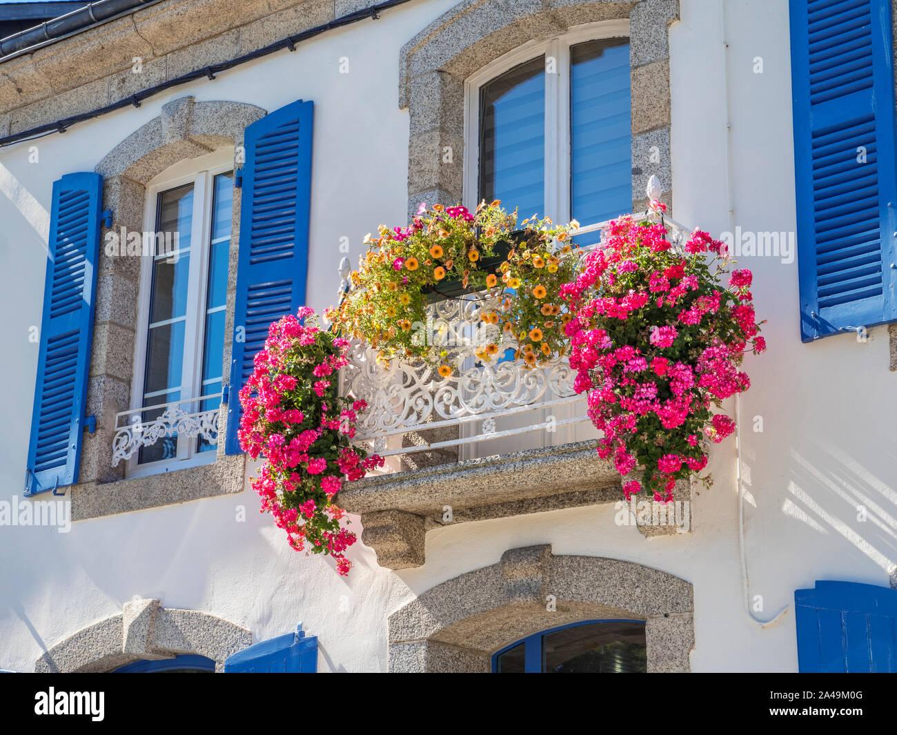 PONT AVEN Maison de Maître 'mansion' con abundantes flores coloridas balcón y ventanas con contraventanas azules tradicionales Pont Aven Bretaña Francia Foto de stock