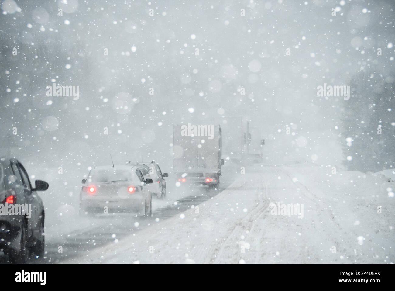 Él coche está circulando por una carretera de invierno en una ventisca Foto de stock