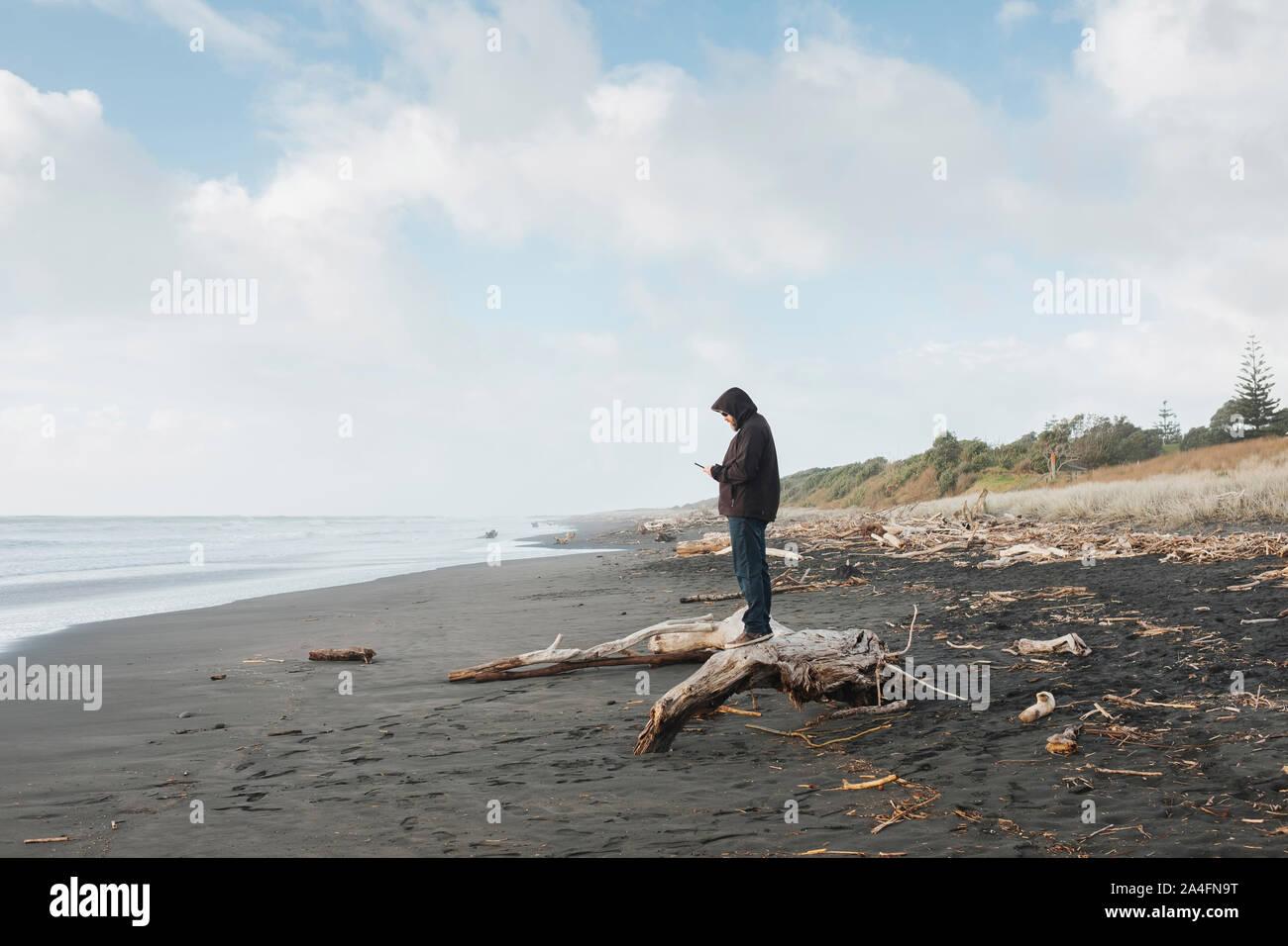 Hombre de pie en driftwood mirando el teléfono móvil en la playa. Foto de stock