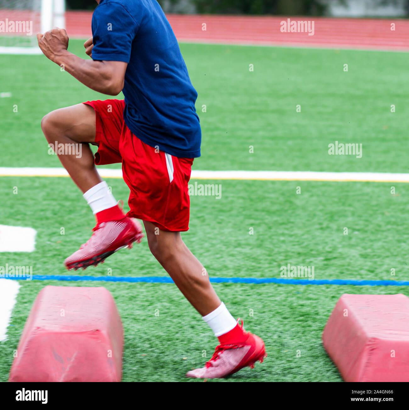 Un Afroamericano jugador de fútbol americano a nivel high school está ejecutándose sobre barreras rojas durante el campamento de verano de la práctica. Foto de stock
