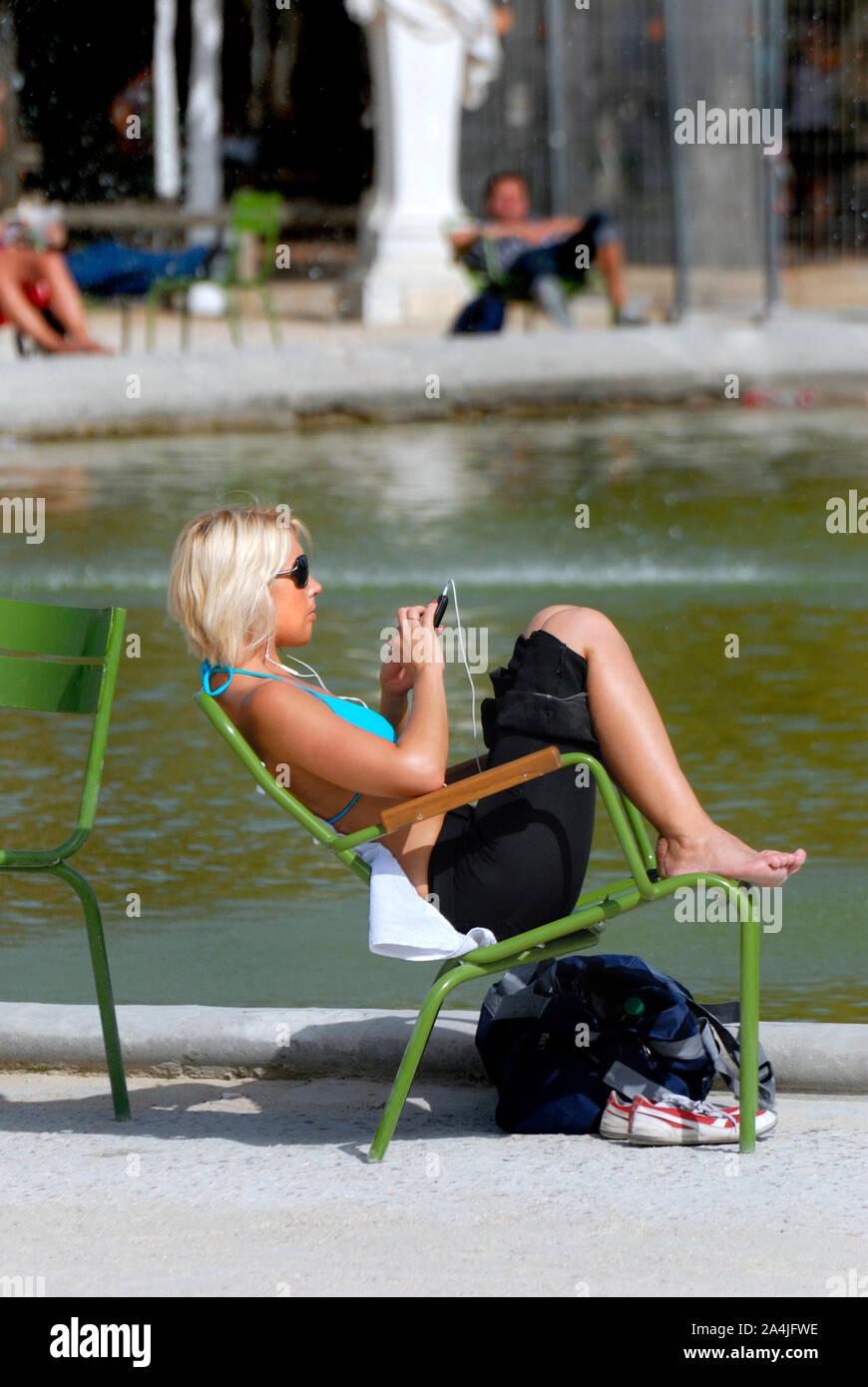 París, Francia. Los Jardins des Tuilleries. Mujer joven relajándose en el estanque Foto de stock