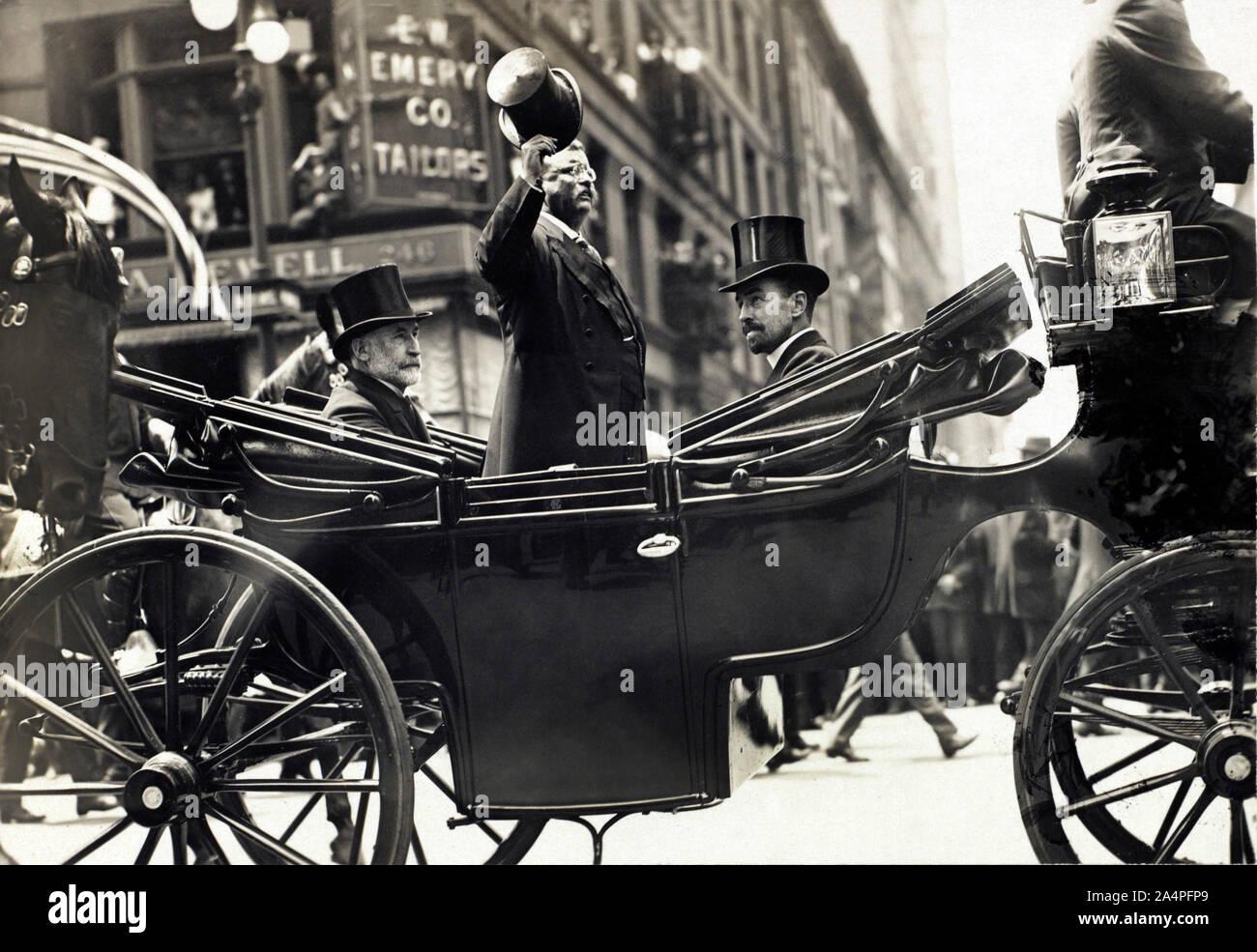 Theodore Roosevelt en pie en el carro con su sombrero inclinado mientras el alcalde de Nueva York, William Gaynor y Cornelius Vanderbilt permanecer sentado durante su homecoming recepción después de su viaje al extranjero, la ciudad de Nueva York, Nueva York, Estados Unidos, junio de 1910 Foto de stock