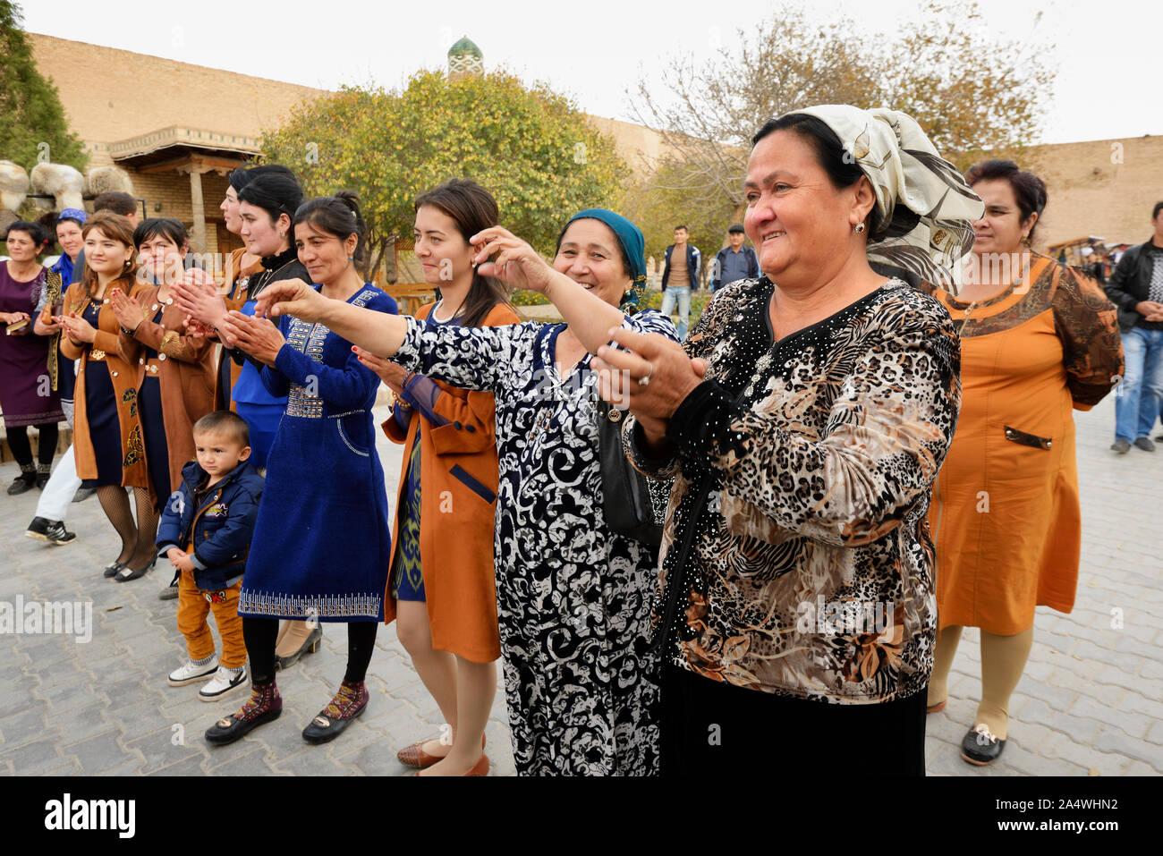 Los huéspedes de baile durante una boda en la calle principal del casco antiguo de la ciudad de Khiva, un sitio muy popular para todas las festividades en la ciudad. Uzbekistán Foto de stock