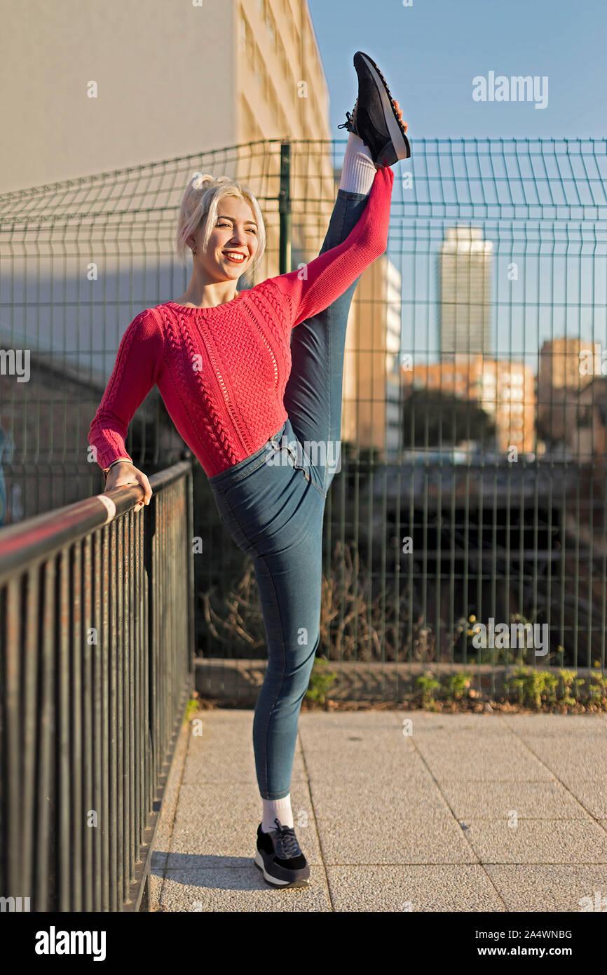 Hermosa chica en un par de pantalones vaqueros en el estilo de ballet ¿las divisiones Foto de stock