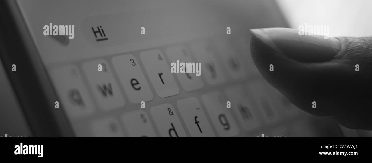 La mano del hombre blanco escribir en un smartphone un mensaje Hi Foto de stock
