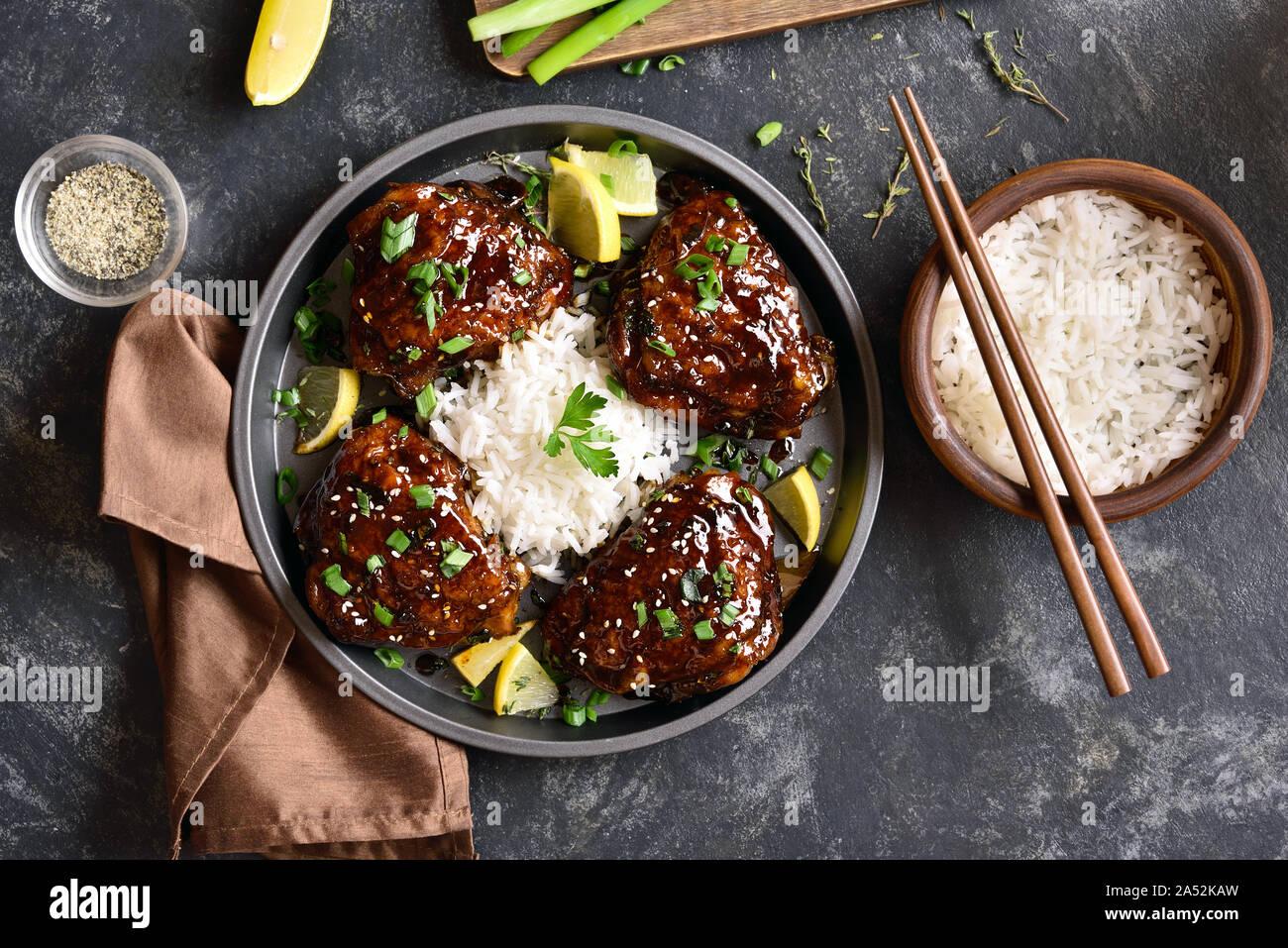 Dulce y picante miel muslos de pollo asado con arroz en mesa de piedra oscura. Comida sabrosa en un estilo asiático. Vista superior, laicos plana Foto de stock