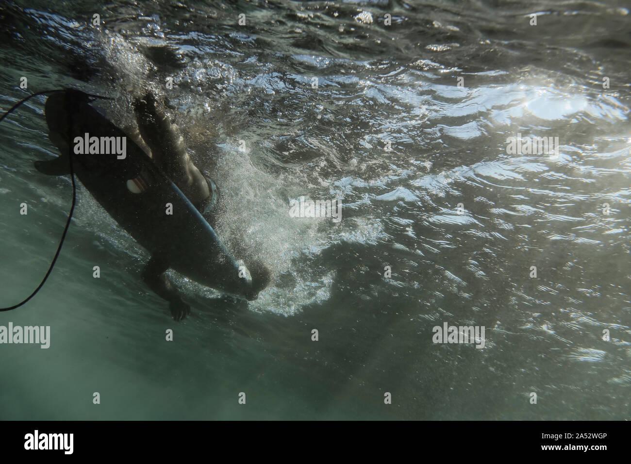 Bajo el agua vista de onda, surfer sentados sobre tablas de surf, filmación subacuática, Sumbawa, Indonesia Foto de stock