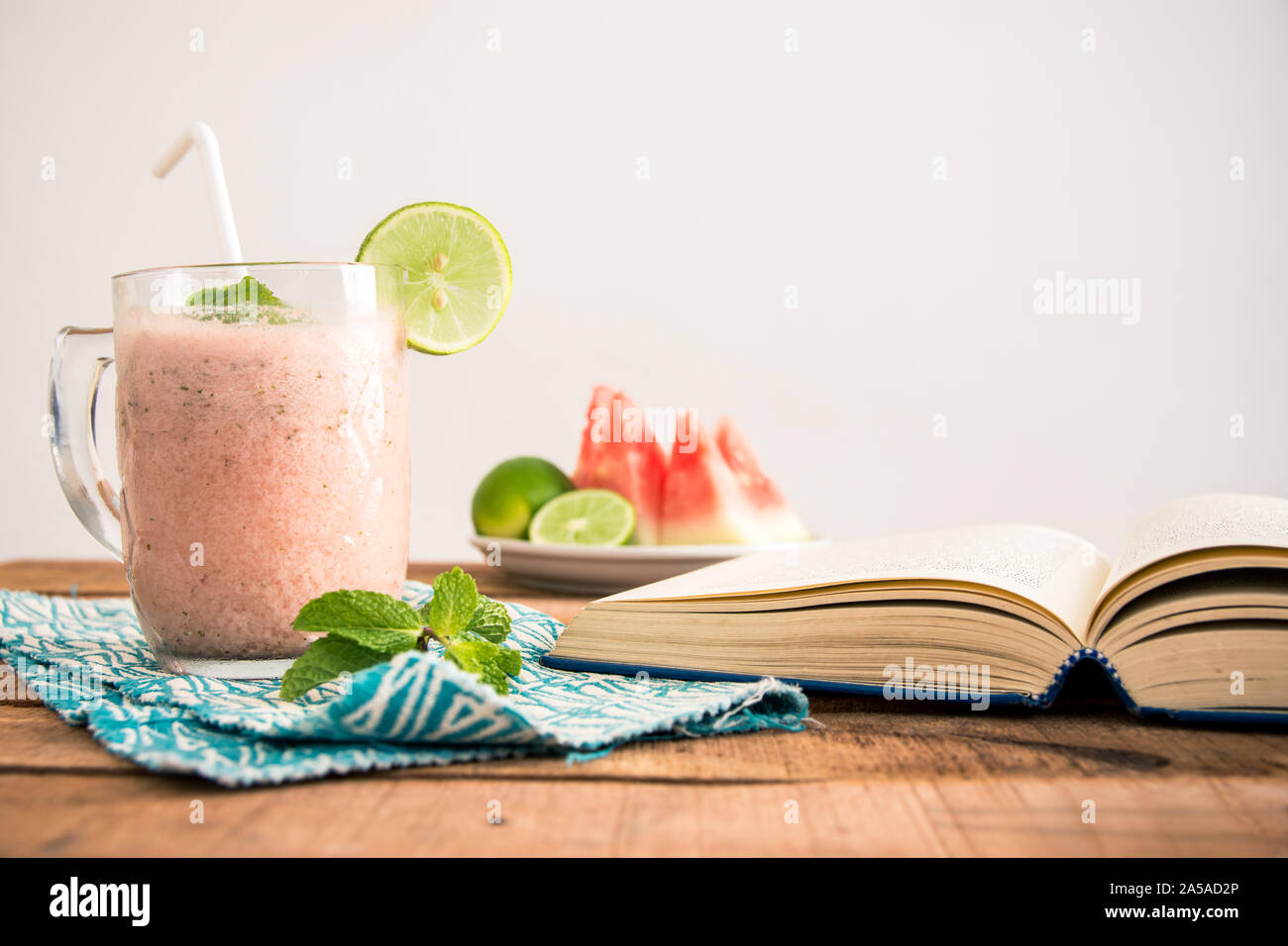Una plana cuadrada (laicos ración) Foto con mesa de desayuno batido de sandía, libro de teléfono y rodajas de frutas en la placa -alimentos y dietas concepto imagen. Foto de stock