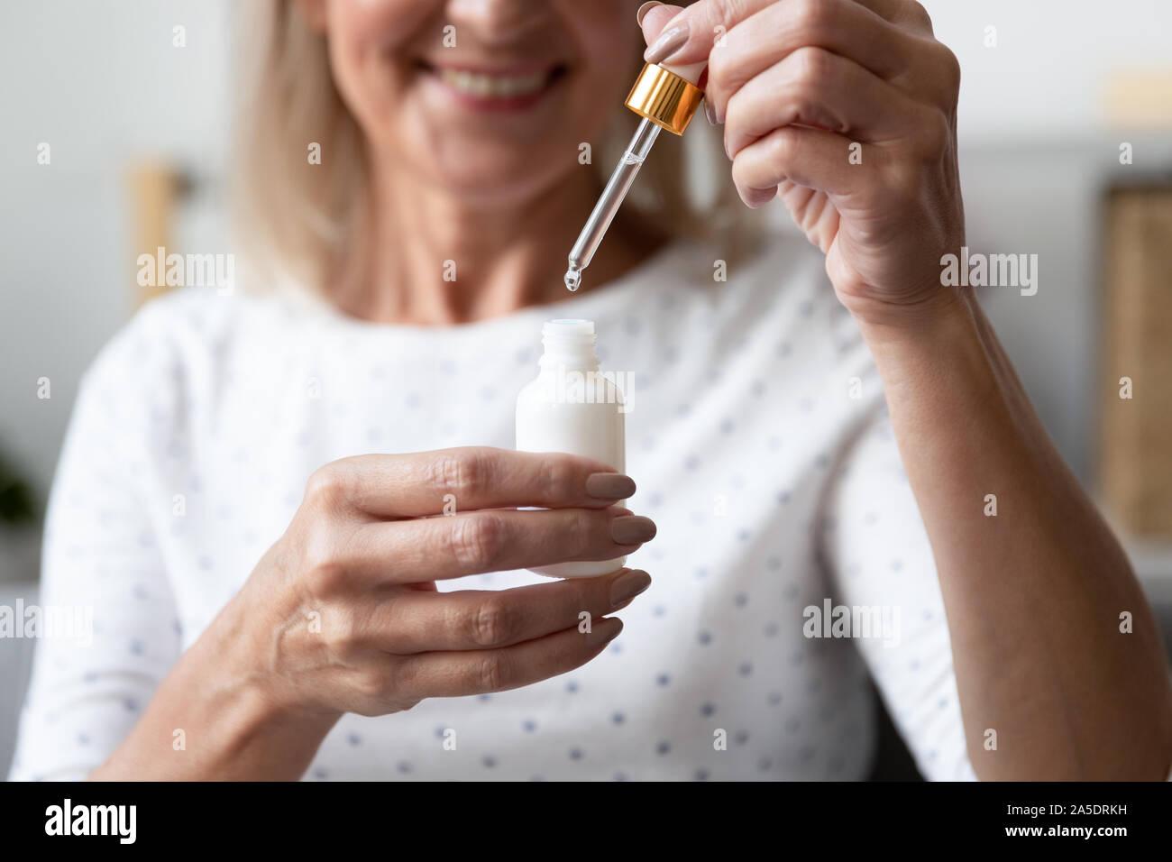 Mujer madura feliz celebración cara suero para el cuidado de la piel, cerrar Foto de stock