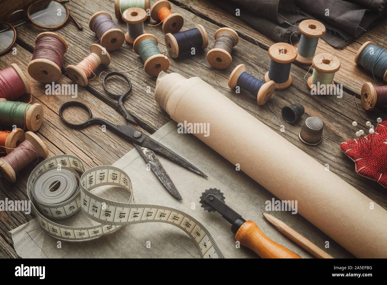 Elementos de costura: retro sastrería tijeras, cinta métrica, dedal de madera, bobinas de hilo, los patrones en papel, corte de cuchilla, cojín para incluyendo los polos Foto de stock