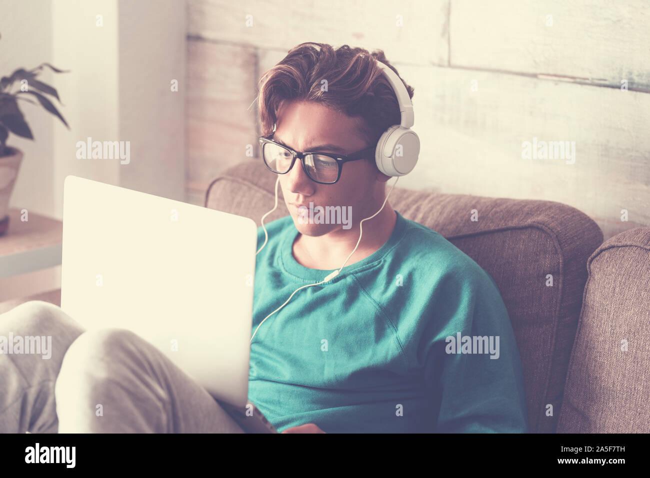 Joven estudiante en casa con un moderno equipo portátil auriculares y estudiar con internet cnnection - guapo muchacho sentado en el sofá con tecnología Foto de stock