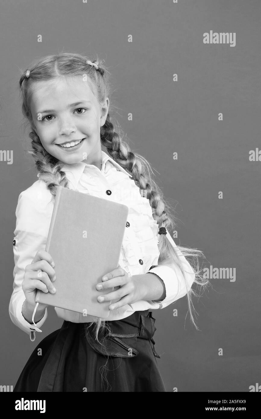 Si el conocimiento que necesita, usted debe leer. Cute little niño sosteniendo un libro sobre fondo rojo, la pequeña niña con conocimiento del libro en las manos. Conocimiento de día o 1 de septiembre. La acumulación de conocimientos, copie el espacio. Foto de stock