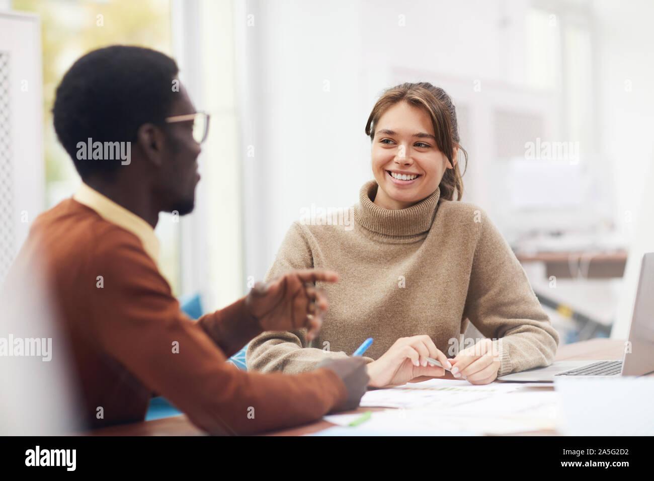 Retrato de hermosa mujer sonriente joven felizmente mientras disfruta de clase en la universidad y hablando a afroamericanos classmate, espacio de copia Foto de stock
