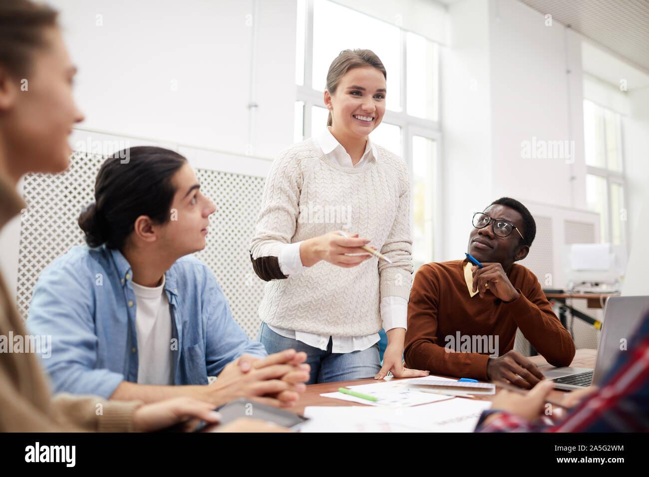 Grupo multiétnico de estudiantes que trabajan juntos en equipo de proyecto mientras estudiaba en la universidad, se centran en la partida chica sonriente reunión Foto de stock
