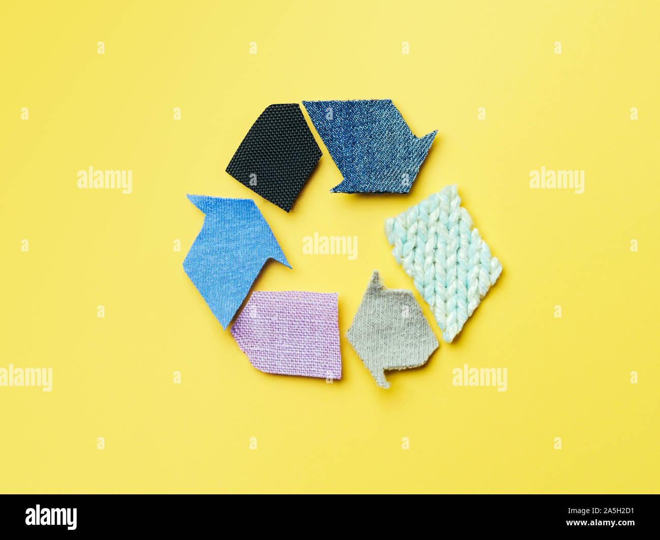 Reducir, reutilizar, reciclar el concepto de fondo. Símbolo de reciclado de ropa usada sobre fondo amarillo. Vista superior plana o de laicos. Foto de stock