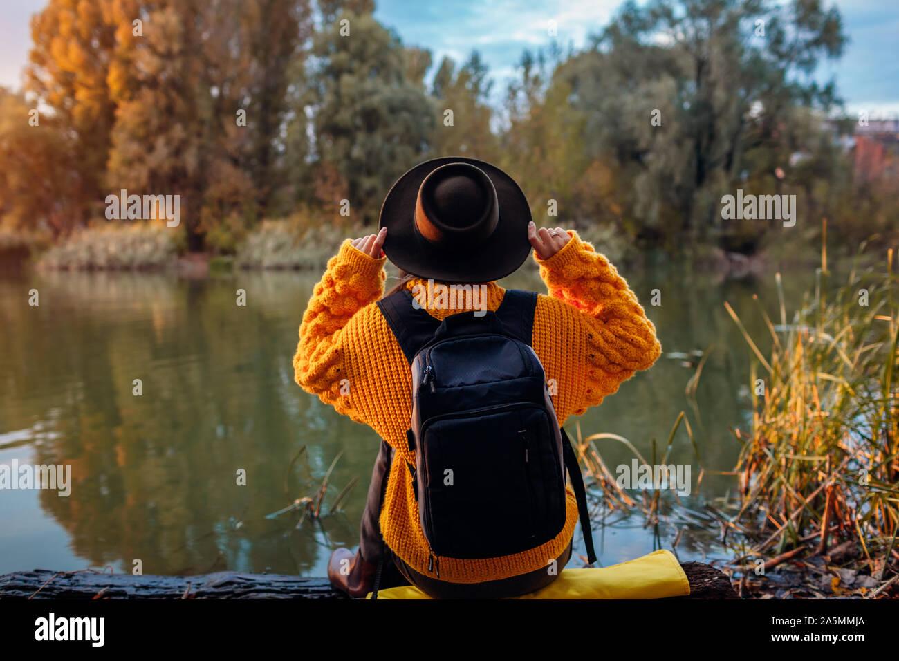Viajero con mochila relajando en otoño de río al atardecer. Mujer joven sentado en banco y relajante la celebración de HAT. Un estilo de vida activo Foto de stock