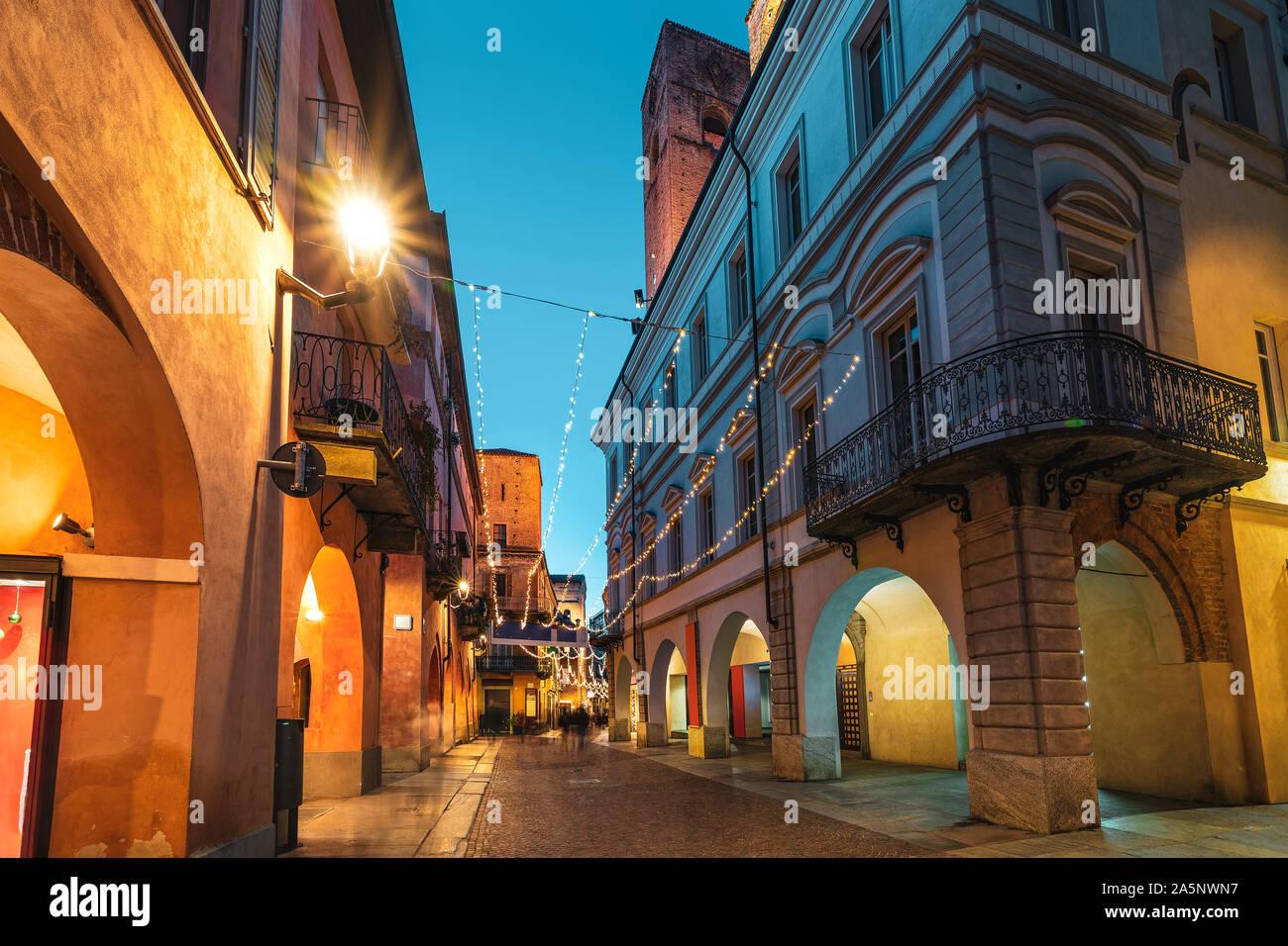Calle peatonal adoquinada iluminada de noche en el casco antiguo de la ciudad de Alba, Piamonte, Norte de Italia. Foto de stock