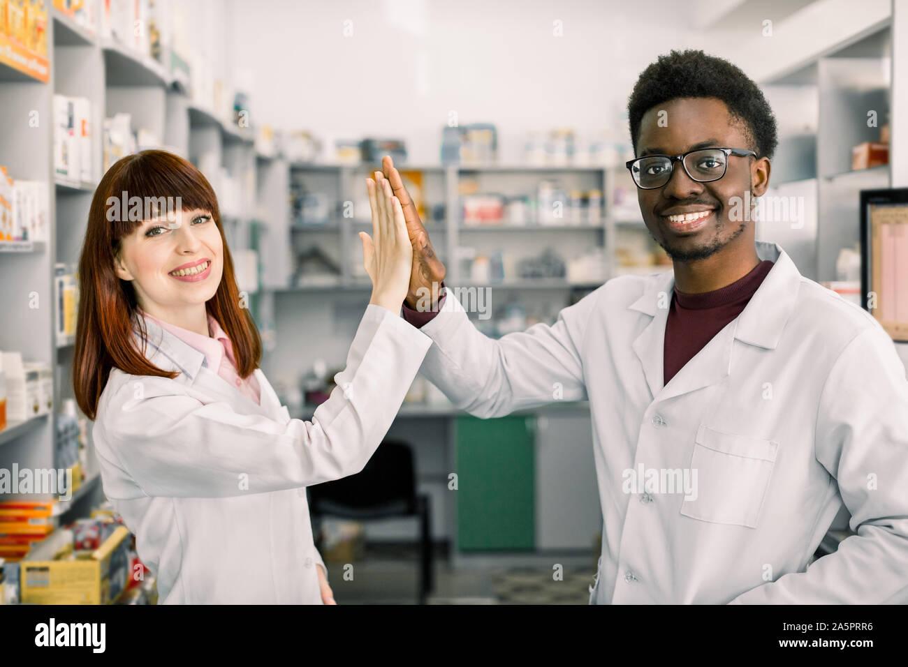 Dos farmacéuticos colleages feliz, hombre y mujer caucásica africanos trabajan en farmacia, sonriente, dando cinco y divertirse. Foto de stock