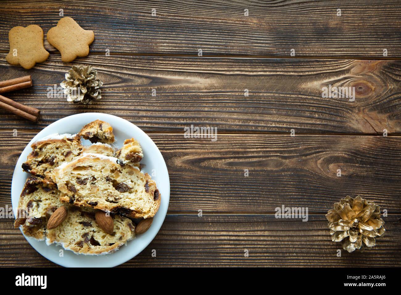 Pastel de Navidad y gingerbread cookies en tabla de madera marrón. Conos de oro y canela decoraciones. Espacio libre para el texto. Espacio para un saludo Foto de stock