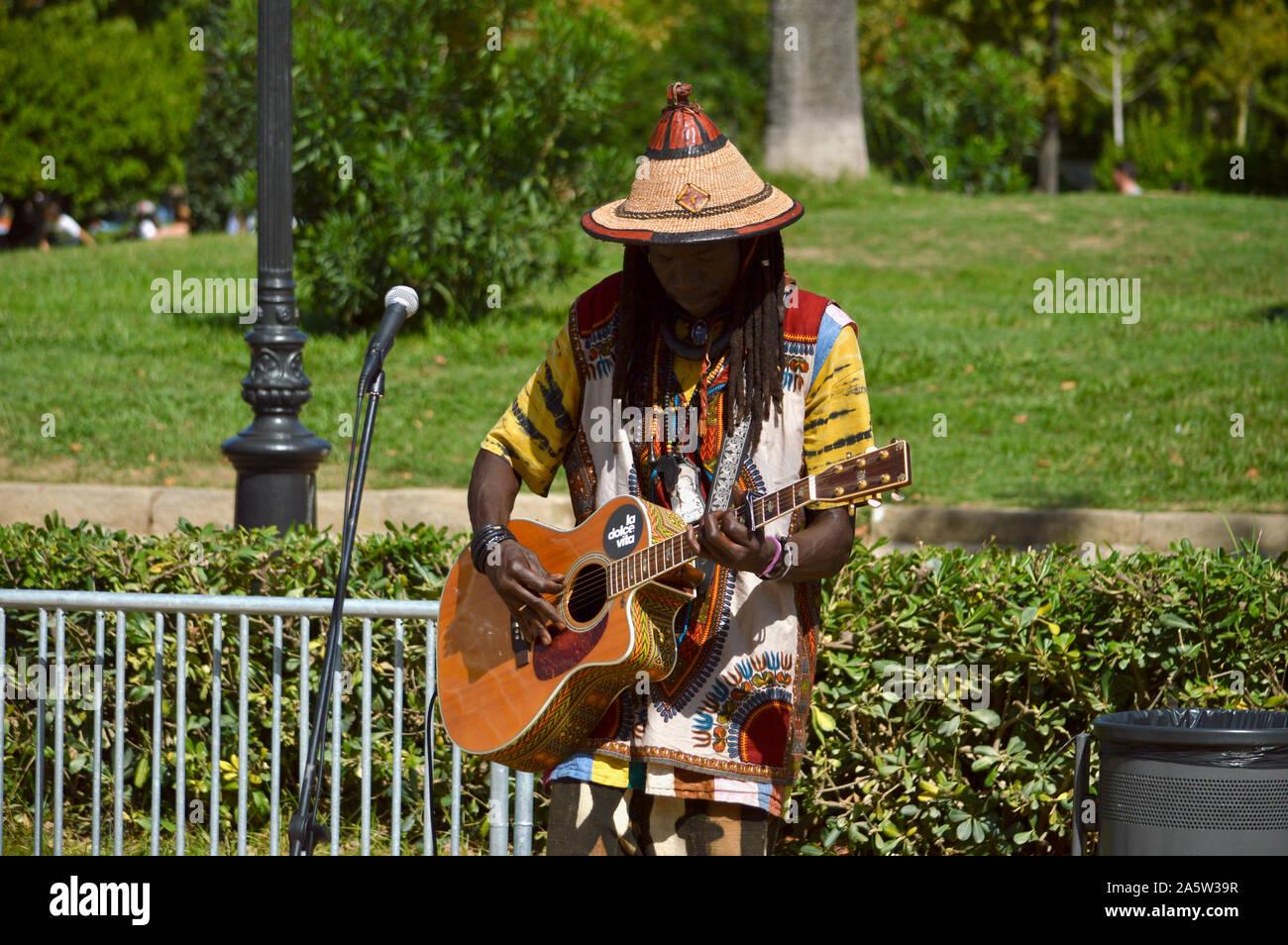 Un músico callejero tocando una guitarra en el Parque de la Ciutadella DURANTE LA MERCE 2019 en Barcelona, España Foto de stock