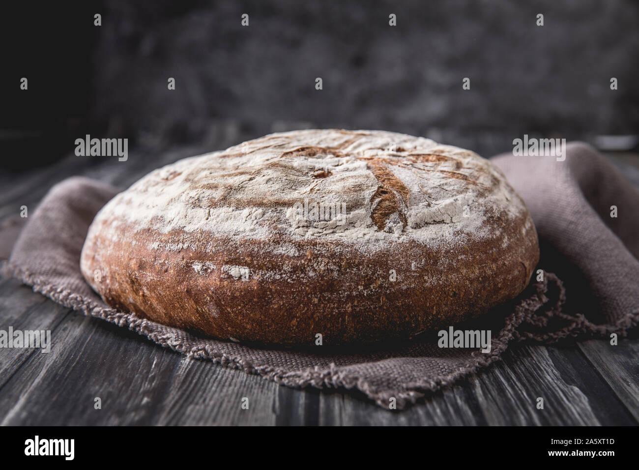 Una ronda de caseros levain pan con harina de centeno y trigo. que se coloca sobre una mesa de madera oscura, con un fondo oscuro. Hay una tela suave marrón Foto de stock