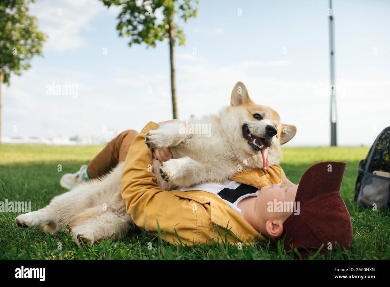 Chico con Welsh Corgi Pembroke en un parque Foto de stock