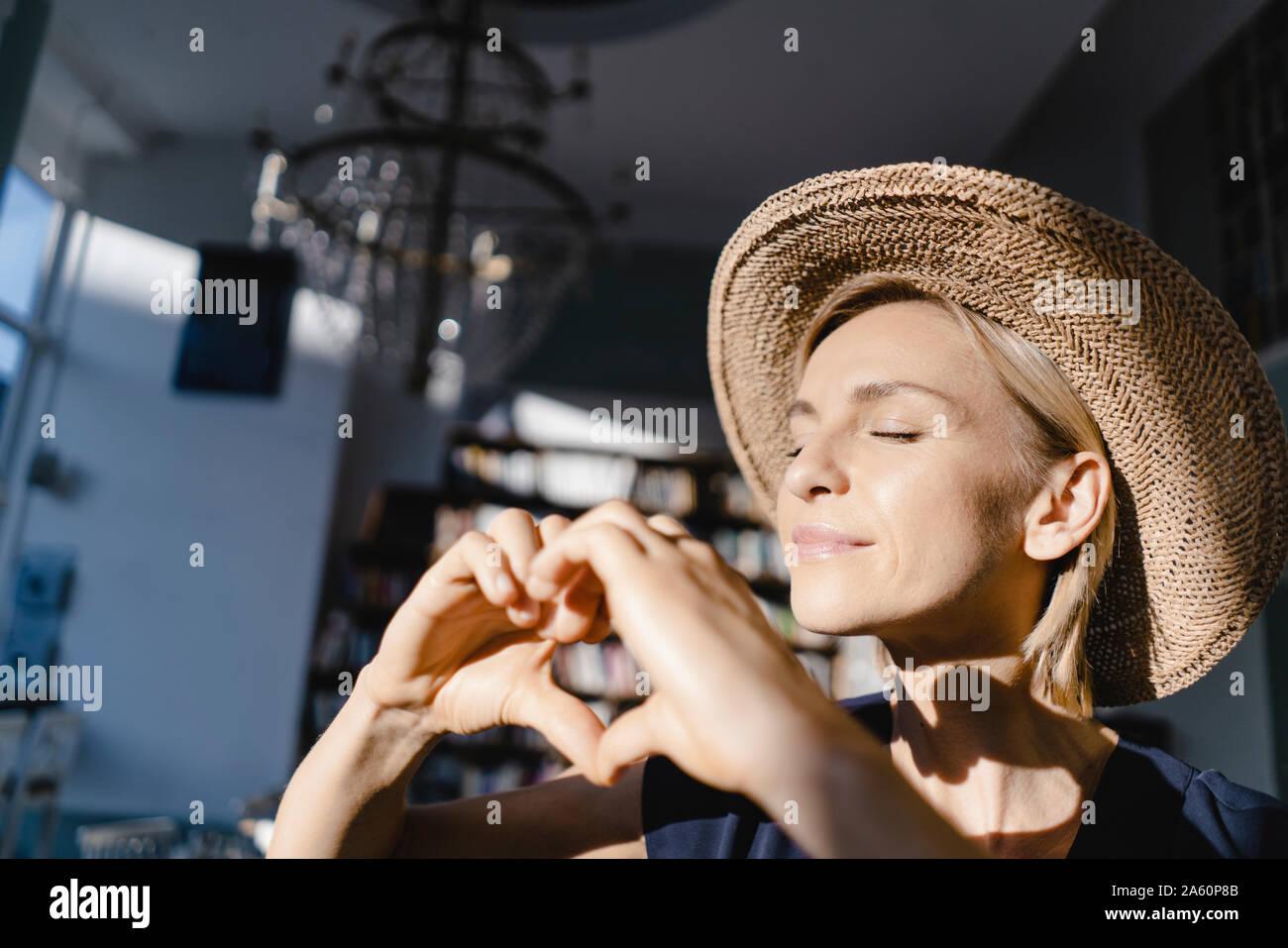 Mujer con sombrero de paja, mirando hacia el sol, haciendo dedo en forma de corazón frame Foto de stock