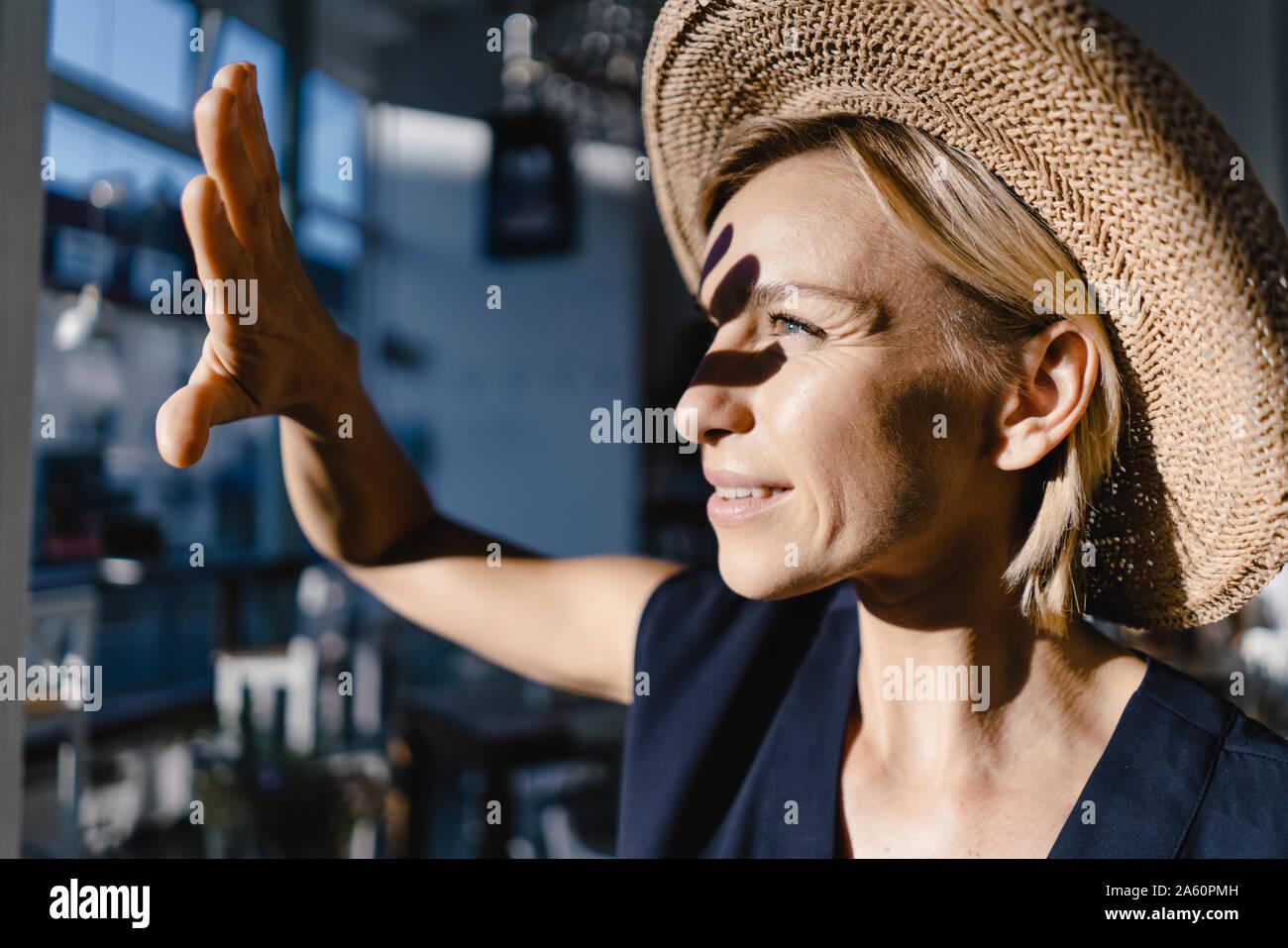 Mujer vistiendo staw hat, protegiendo su rostro del sol Foto de stock