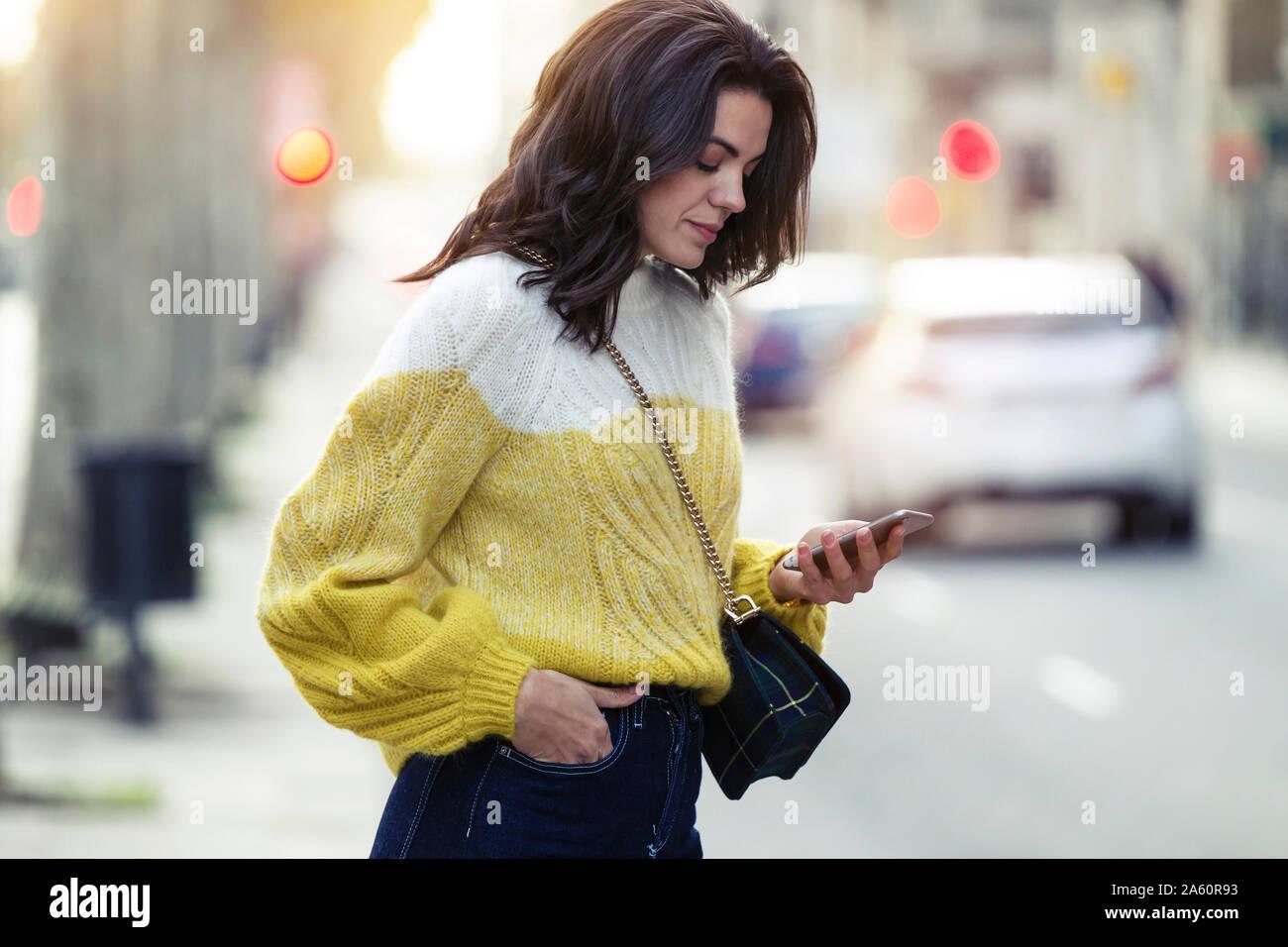 Mujer morena utilizando su smartphone en la ciudad Foto de stock