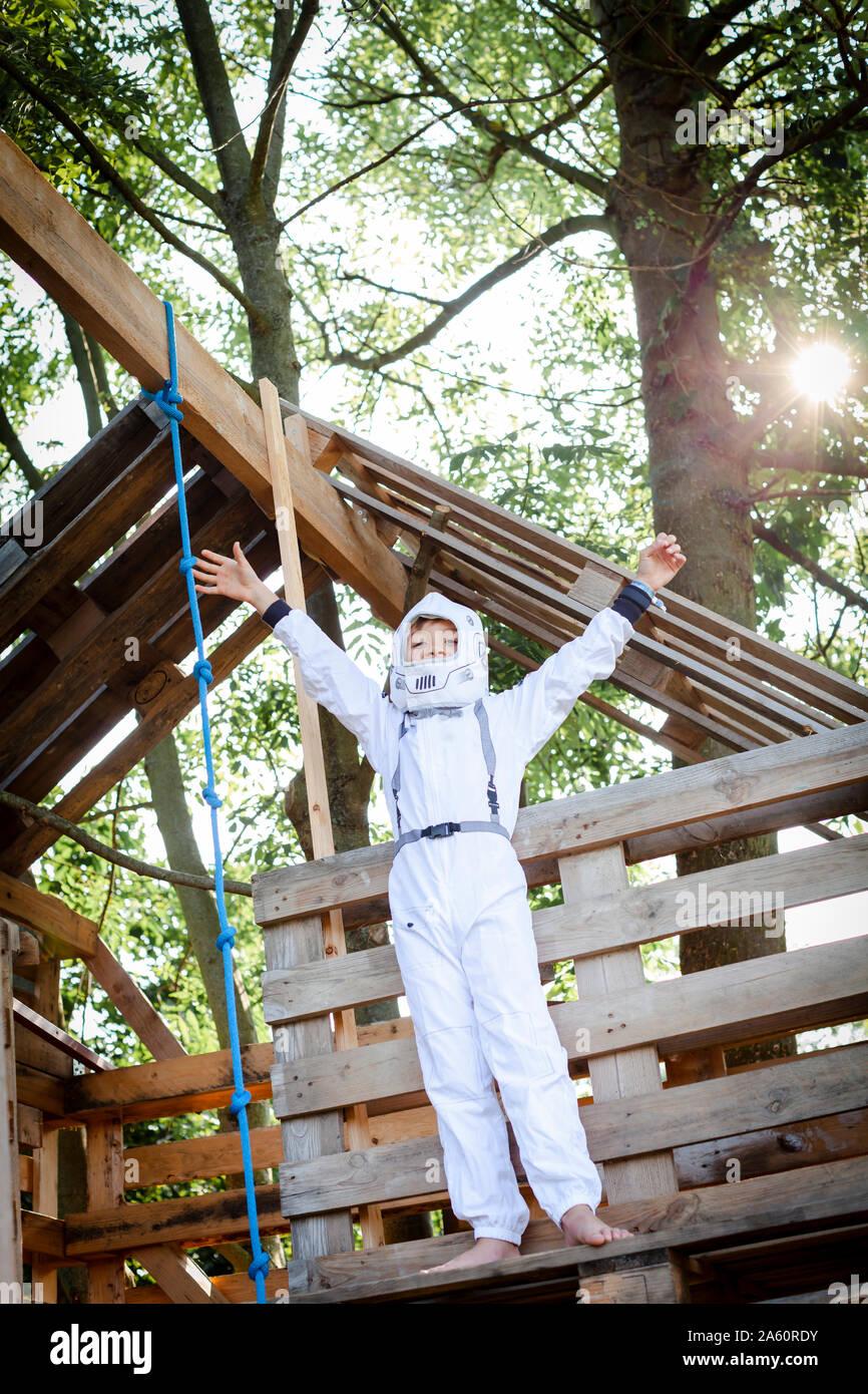 Joven como un superhéroe, el astronauta jugando en una casa en el árbol Foto de stock