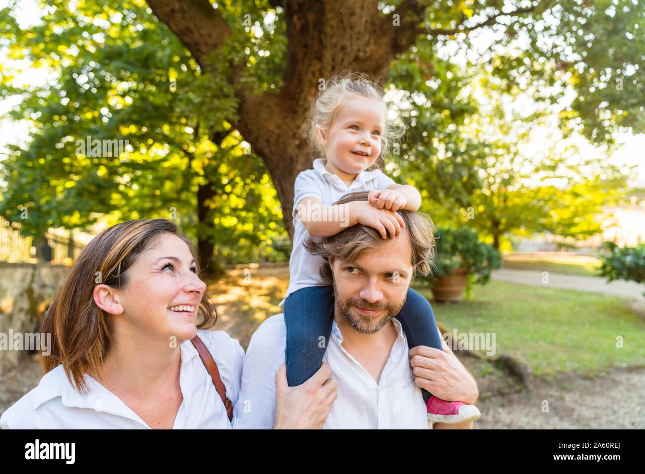 Familia feliz en un parque con el padre llevando sobre sus hombros una hija pequeña Foto de stock