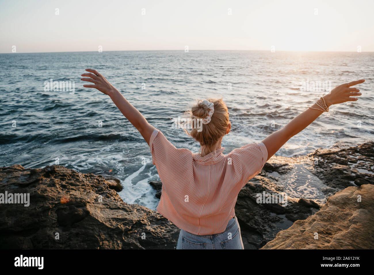 Vista trasera de la mujer joven en el mar con brazos levantados, Sunset Cliffs, San Diego, California, EE.UU. Foto de stock