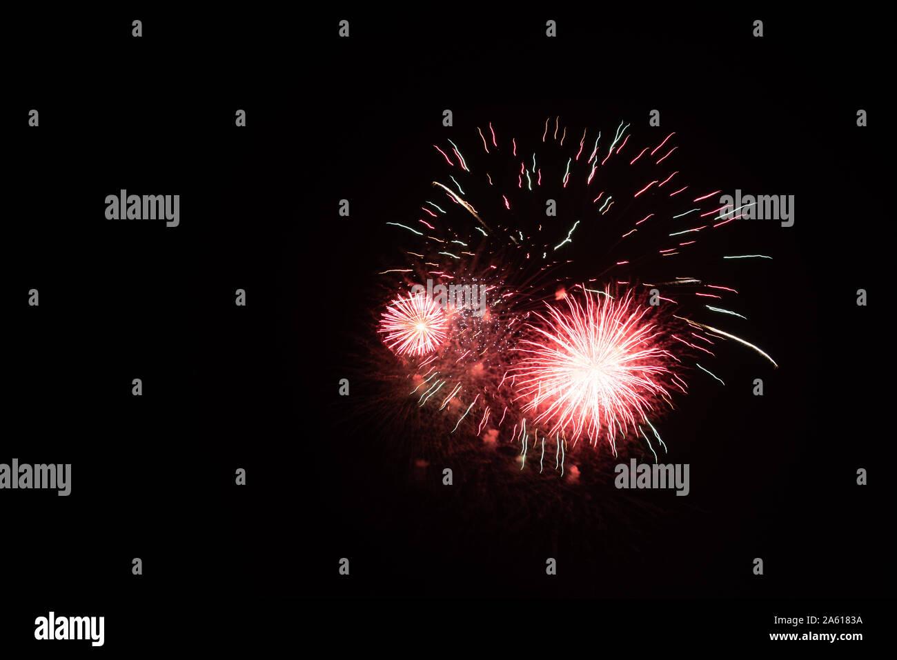 Fotografiar fuegos artificiales en el cielo de la noche con un tiempo de exposición y el negro como color de fondo de imagen de alta calidad para pc buenos antecedentes e impresiones artísticas. Foto de stock