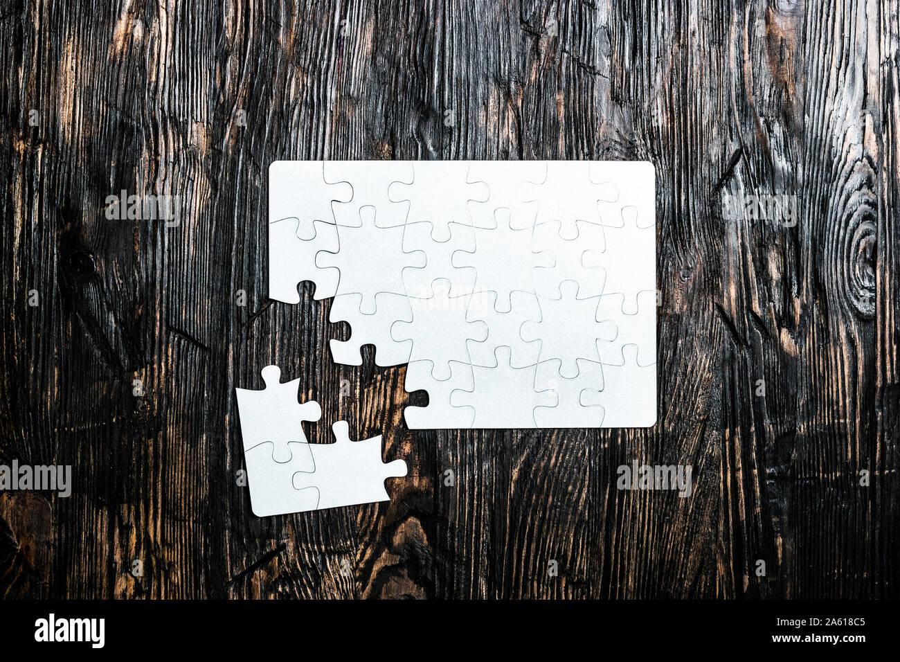 Puzzle blanco inconclusa sobre la mesa de madera oscura vista superior Foto de stock