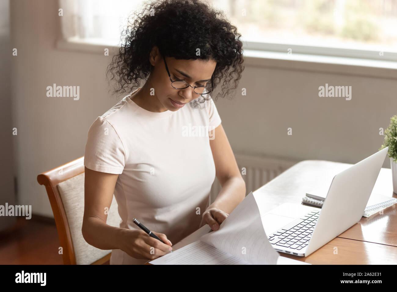 Concentrado afroamericano joven mujer de negocios que la firma de los documentos, los seguros médicos. Foto de stock