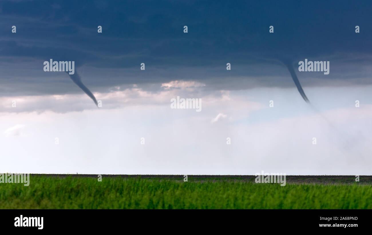 Las nubes embudo gemelas aparecen en un campo como un par de tornados landspout se desarrollan a partir de una tormenta, cerca de San Francisco, Kansas, Estados Unidos. Foto de stock
