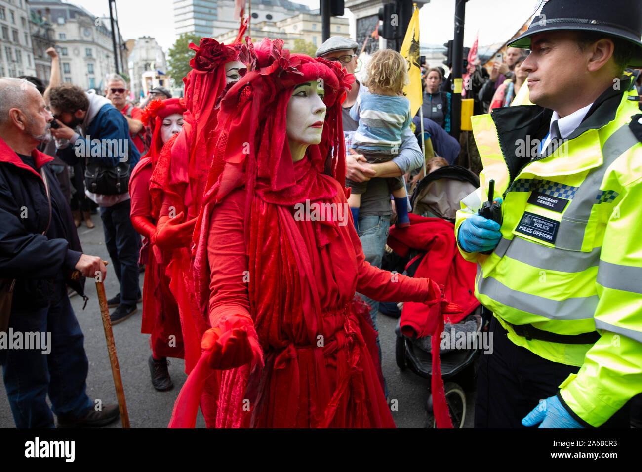 Londres, 10 de octubre de 2019, la extinción rebelión grupo en trajes rojos de policía rodean preparando la detención acivists que han encadenado a una estructura de madera en la carretera junto a Trafalgar Square. Foto de stock