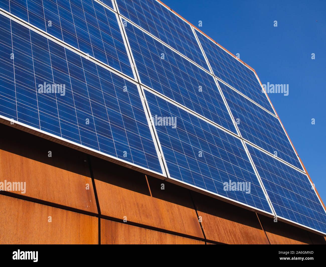 Los paneles solares fotovoltaicos en acero corten el techo de un edificio de la universidad de la ciudad. Foto de stock
