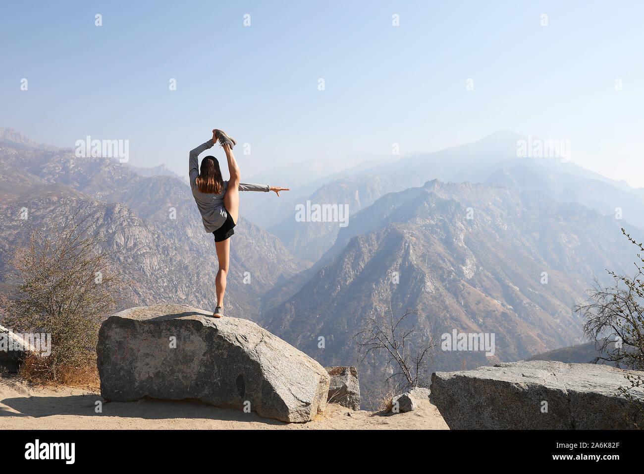 Las hembras jóvenes se involucra en pose de yoga increíble en el pintoresco entorno de montaña. Foto de stock