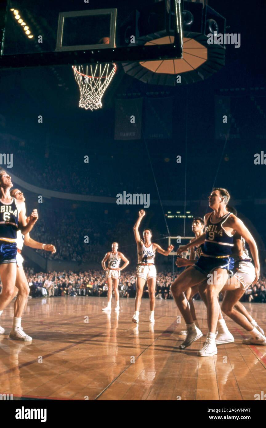 NEW YORK, NY - 3 de noviembre: Carl Braun #4 de los New York Knicks dispara el franco como Neil Johnston Joe Graboski #6 y #9 de los Philadelphia Warriors esperar un repunte durante un partido de la NBA el 3 de noviembre de 1957 en el Madison Square Garden de Nueva York, Nueva York. (Foto por Hy Peskin) (número de registro: X4854) Foto de stock