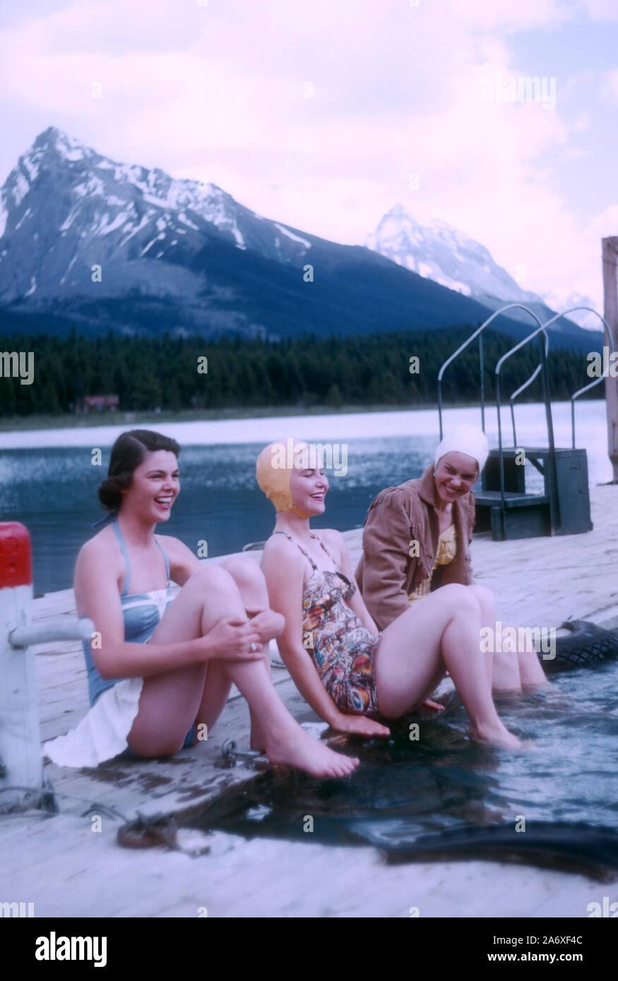 JASPER, AB - Julio, 1954: Vista General como tres mujeres sentadas en un charco de agua durante su Jasper sendero paseo alrededor de julio de 1954 en Jasper, Alberta, Canadá. (Foto por Hy Peskin) (número de registro: X1485) Foto de stock