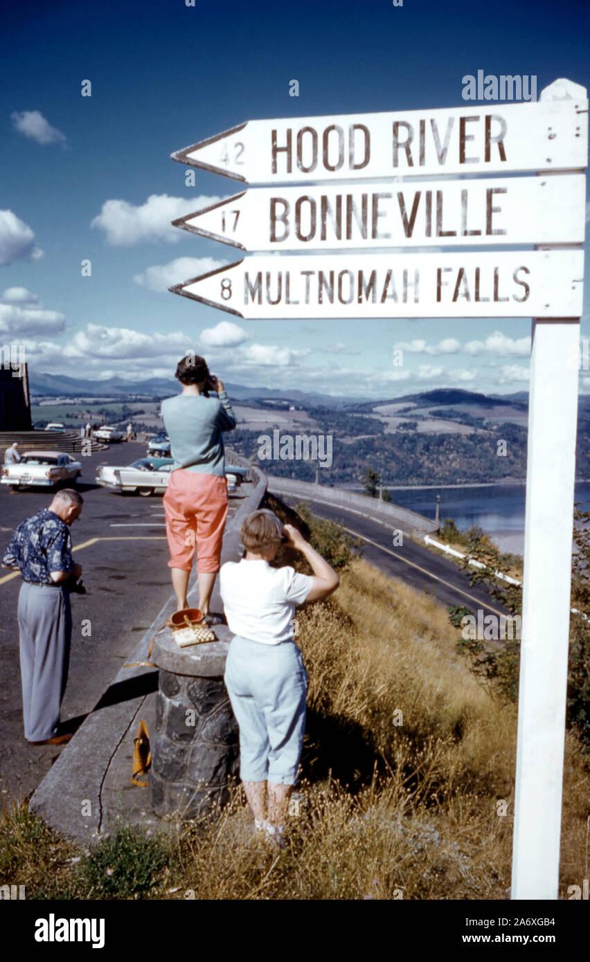 O - 1956: Vista General como la gente mira el río Columbia desde un punto de vista con un signo que muestra hasta qué punto el Hood River, Bonneville Dam y el Multnomah Falls son circa 1956 en Oregon. (Foto por Hy Peskin) Foto de stock