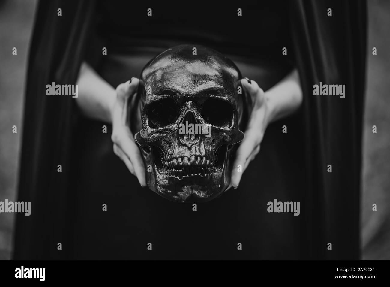 Mujer sostiene el cráneo en manos.la muerte, ritos espirituales concepto, Halloween, horror, miedo símbolo de muertos. Blanco y negro. Foto de stock