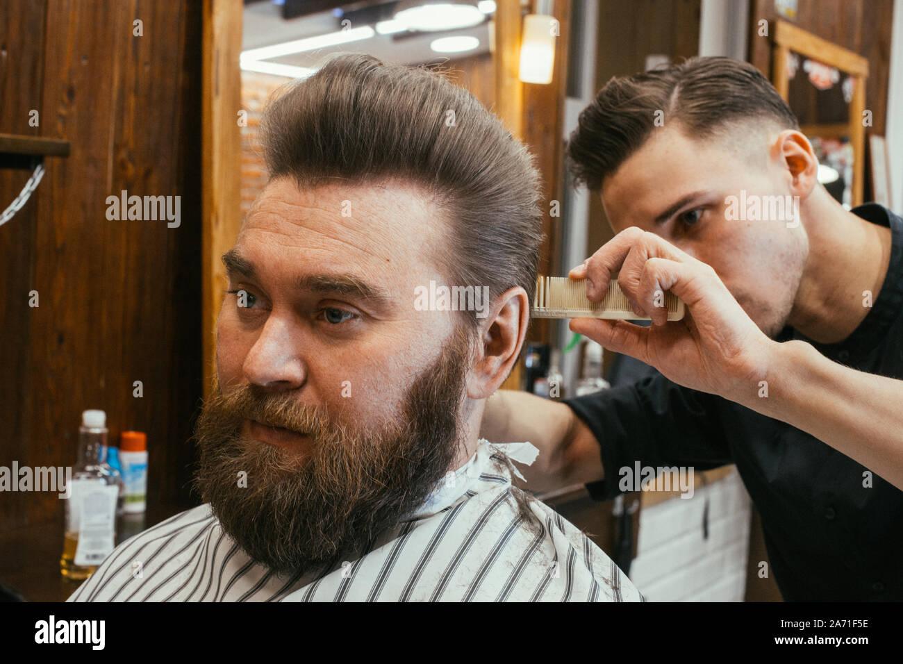 Barber shop, un hombre con una barba corta peluquería. Un pelo bonito y cuidado, peluquería para hombres. Corte de pelo profesional, peinado y estilo retro. Custo Foto de stock